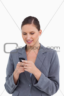 Close up of smiling tradeswoman typing text message
