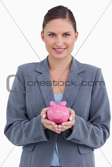 Smiling bank clerk holding piggy bank