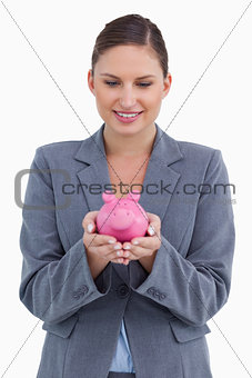 Smiling bank clerk with piggy bank