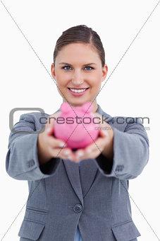 Smiling bank clerk offering piggy bank