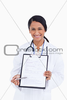 Close up of smiling female physician pointing at form