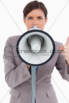 Close up of angry female entrepreneur shouting through megaphone