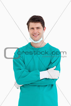 Close up of smiling male doctor in scrubs with folded arms
