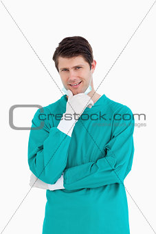 Close up of male doctor wearing scrubs in thinkers pose