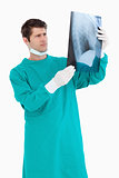 Close up of male doctor wearing scrubs looking at x-ray