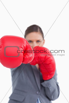 Attacking fist of tradeswoman in boxing glove