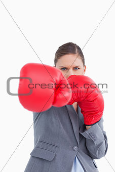 Tradeswoman with boxing gloves attacking with right fist