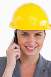 Close up of female architect with helmet on her cellphone
