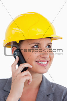 Close up of female architect with cellphone and helmet on