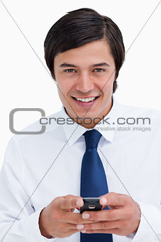 Close up of smiling tradesman holding his cellphone
