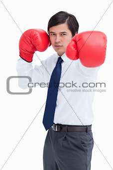 Young tradesman with boxing gloves striking