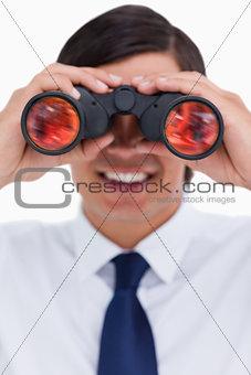 Close up of smiling tradesman looking through binoculars