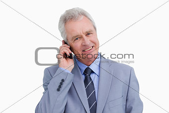 Close up of smiling mature tradesman on his mobile phone