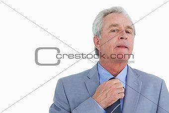 Close up of mature tradesman adjusting tie