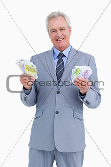 Smiling mature tradesman with cash in his hands