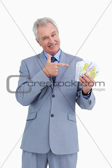 Mature tradesman pointing at his money