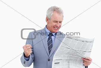 Mature tradesman cheering about news paper article