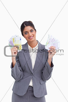 Smiling female entrepreneur holding bank notes