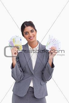 Smiling female entrepreneur holding bank notes