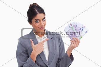 Female entrepreneur pointing at money in her hand