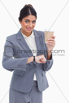 Smiling female entrepreneur with paper cup just checked the time