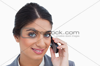 Close up of smiling female entrepreneur on her mobile phone