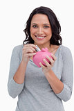 Smiling woman putting money into her piggy bank