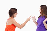Teenage girl harshly pointing her finger at her surprised friend