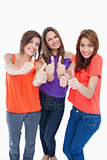 Teenage girls showing their happiness by putting their thumbs up