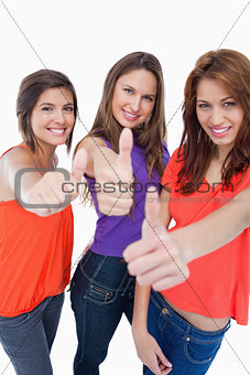 Three teenage girls proudly showing their happiness by putting t