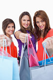 Smiling young women showing their purchases in front of the came