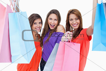 Three teenagers raising their arms while holding their purchases