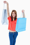 Teenage girl smiling and raising her shopping bags in the air