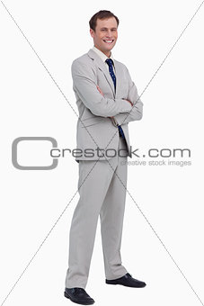 Smiling businessman standing with his arms folded