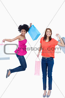 A teenage girl jumping with her shopping bags while her friend i