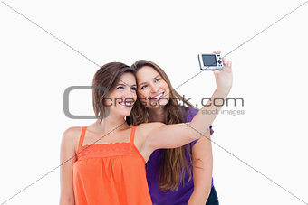 Beaming teenager photographing herself and a smiling friend