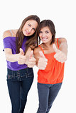 Teenagers putting their thumbs up while smiling