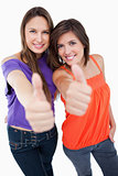 Smiling teenagers giving their thumbs up in approval