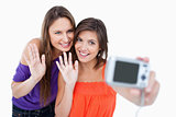 Teenagers waving for a digital camera