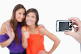 Two teenage girls photographed by a friend holding a digital cam