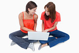 Smiling teenagers sitting cross-legged with a laptop