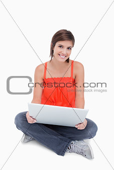 Beautiful teenage sitting cross-legged with a laptop on her legs