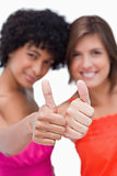 Thumbs up showed by two happy teenage girls