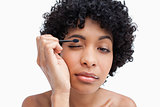 Young woman applying make-up while putting on eye-shadow 