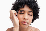 Young woman closing her eyes while applying eye-shadow