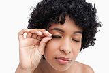 Young brunette placing false eyelashes