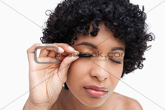 Young brunette placing false eyelashes