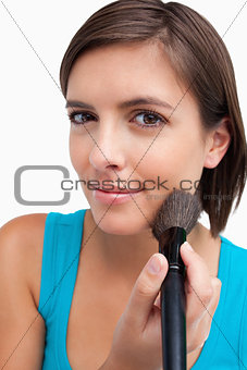 Attractive teenager standing upright while applying make-up with