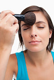 Young calm woman closing her eyes while applying make-up