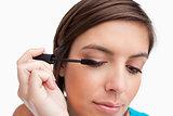 Relaxed teenager carefully applying her mascara on her eye